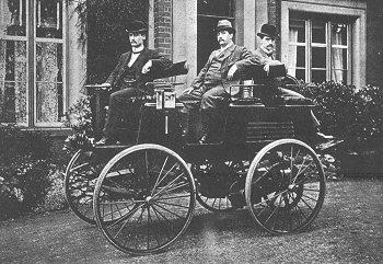 שלושה גברים יושבים על מכונית חשמלית משנת 1895, צילום תקופתי בשחור לבן.